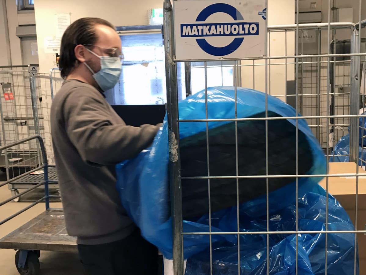 Tatu Mattila nostaa renkaan rullakkoon Matkahuollossa