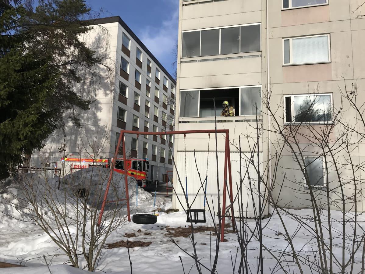 Pelastustyöntekijä seisoo kerrostalon parvekkeella. Parvekkeen alapuolella on lasten keinu.