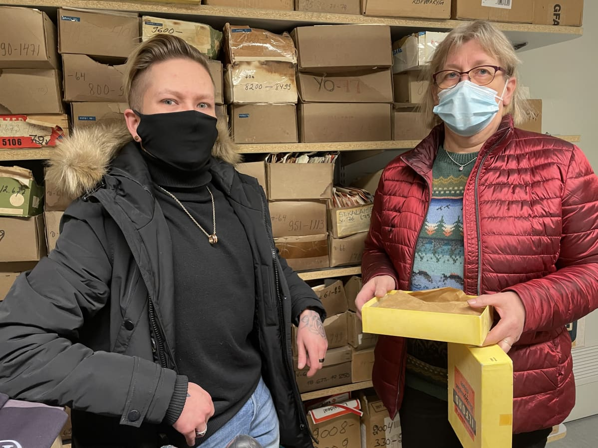 Oulaisten Kuvaamon yrittäjä Petteri Krogerus ja Oulaisten kulttuurituottaja Tuula Aitto-oja seisovat vielä varastossa pahvilaatikoissa olevan valokuvakokoelman edessä.