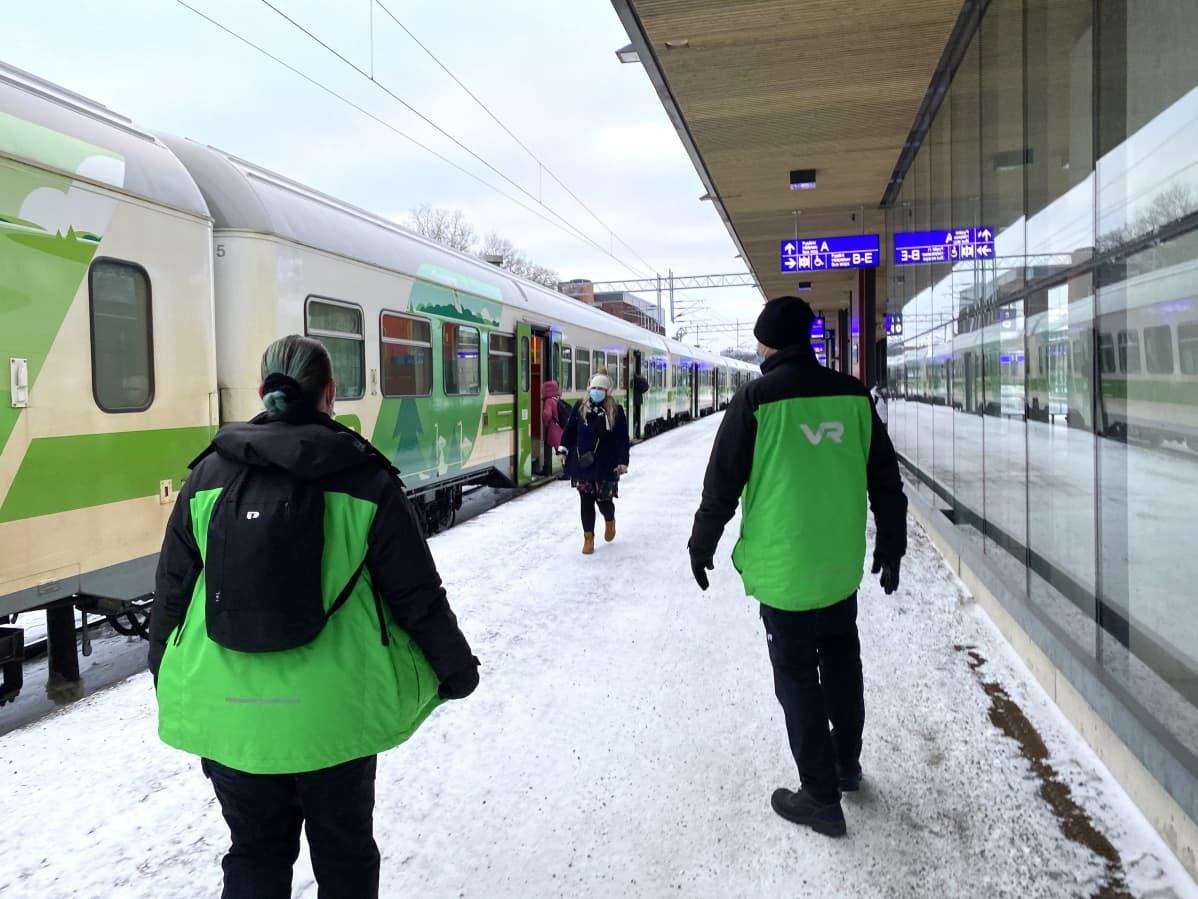 VR:n työntekijöitä ja matkustaja asemalaiturilla Lahdessa.