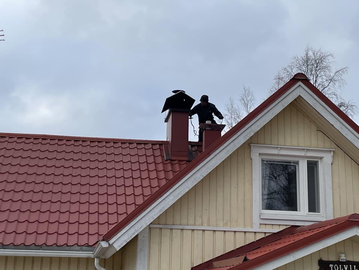 Nuohooja puutalon punaisella katolla.