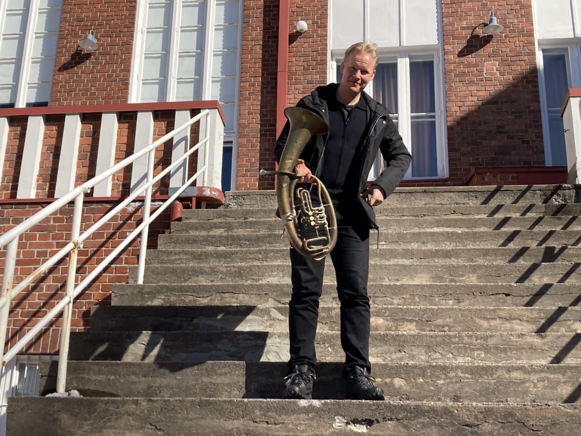 Visa Haarala seisoo Kotkan konserttisalin portailla tuuban kanssa.