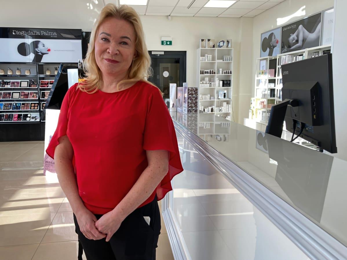 Sf-clinikenin yrittäjä Jaana Saloniemi seisoo tiskin edessä, taustalla kosmetiikkatuotteita.