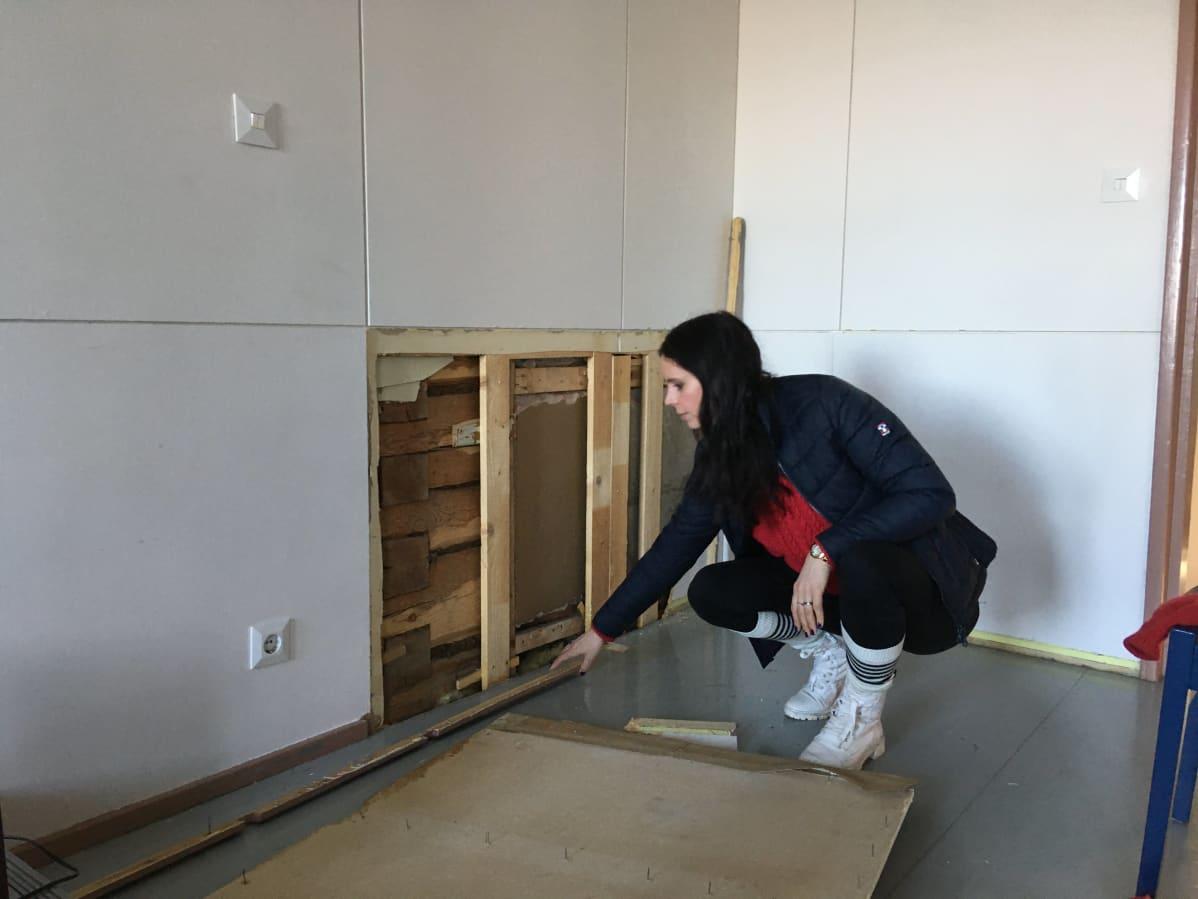 Kyykistynyt nainen tutkii hirsitalon seinää, josta poistettu lastulevyä.