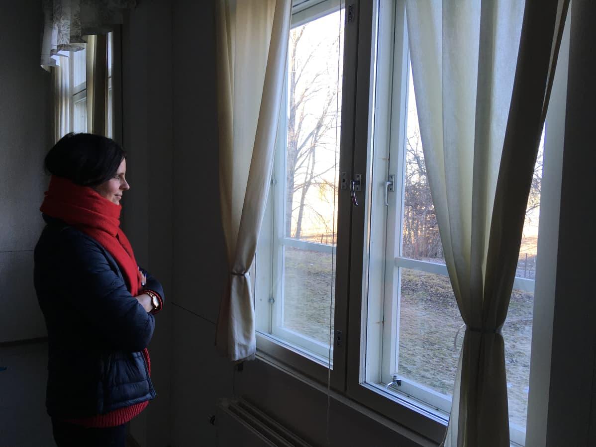 Punaiseen kaulahuiviin kietoutunut nainen katsoo ulos ikkunasta