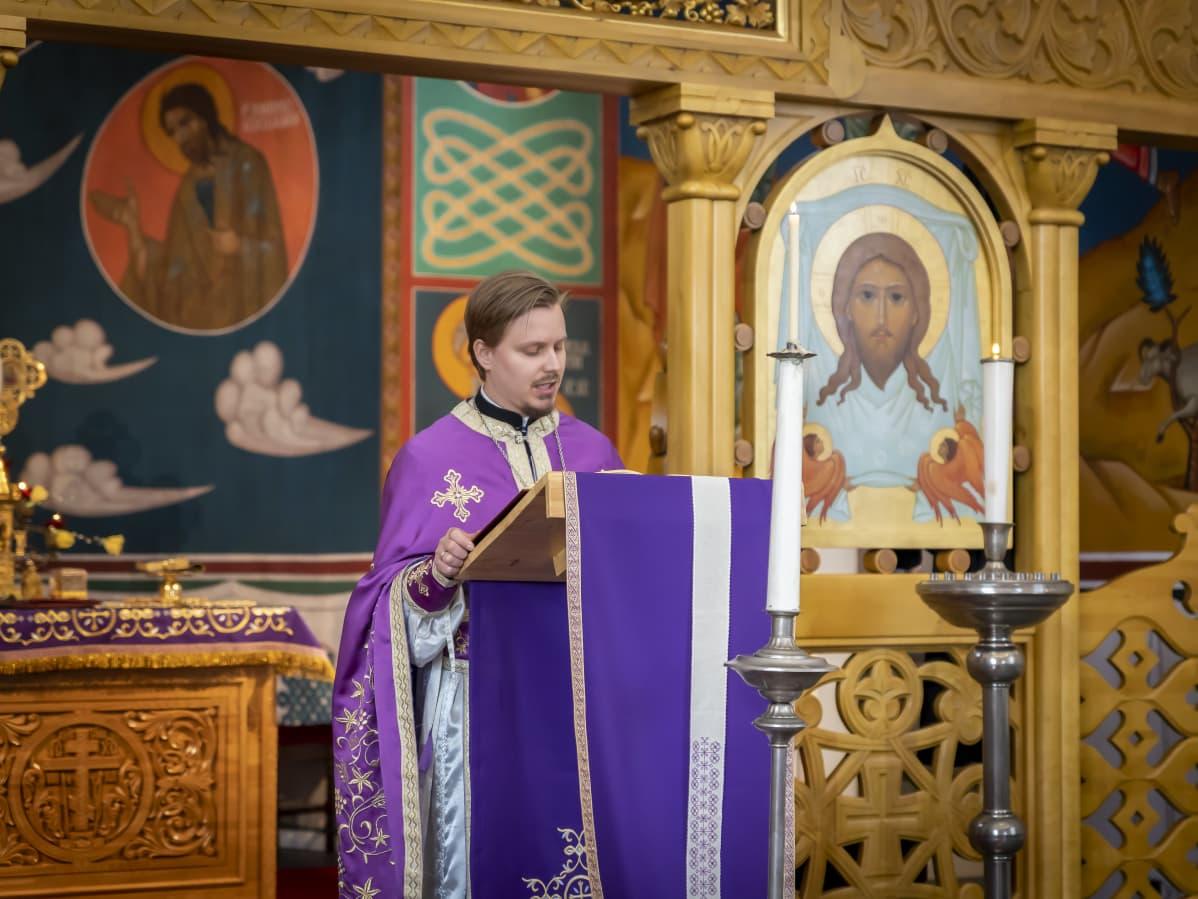 Pappi lukee raamattua ortodoksisessa jumalanpalveluksessa.