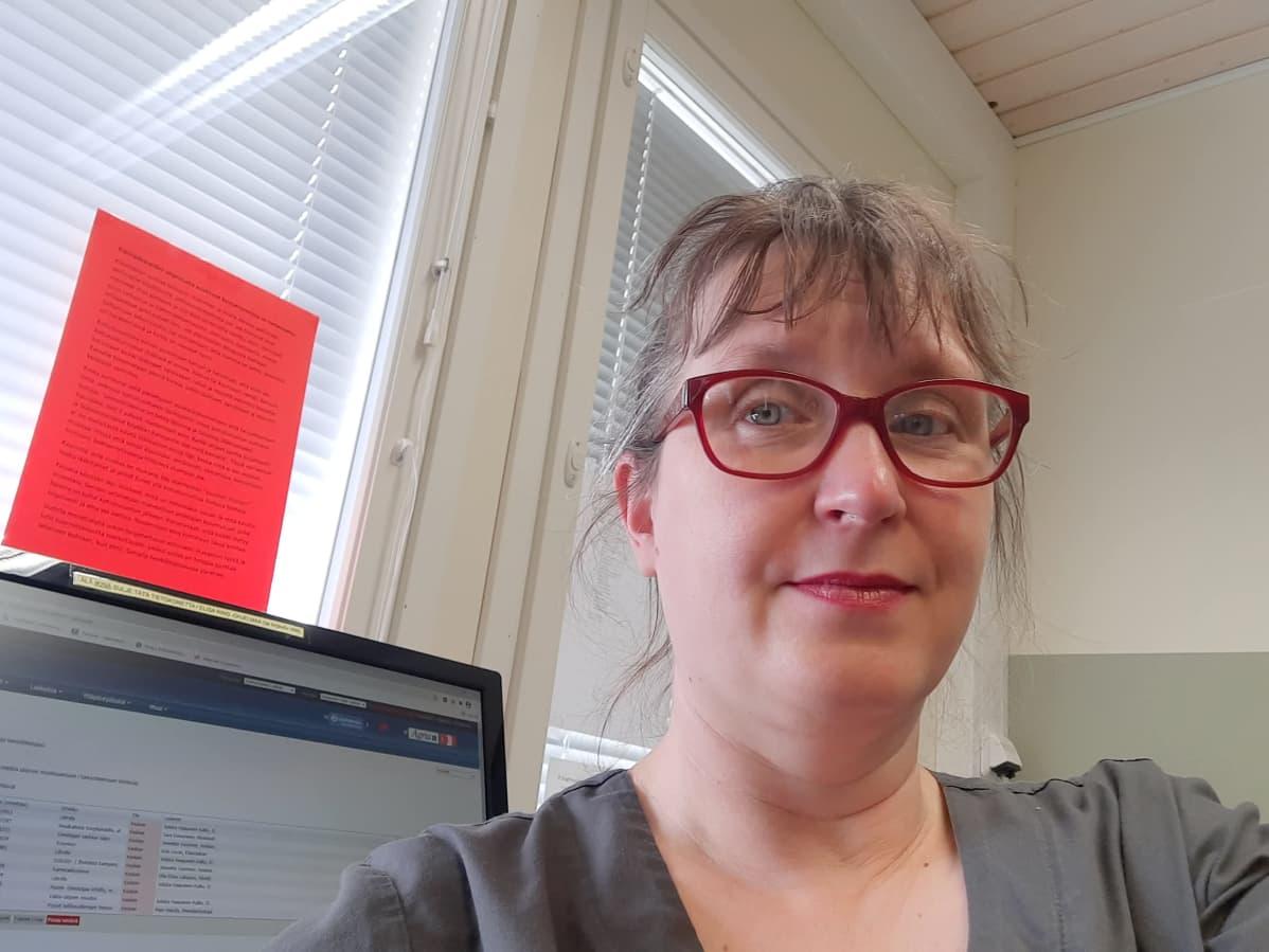 Nainen on ottanut selfien itsestään tietokoneen ääressä