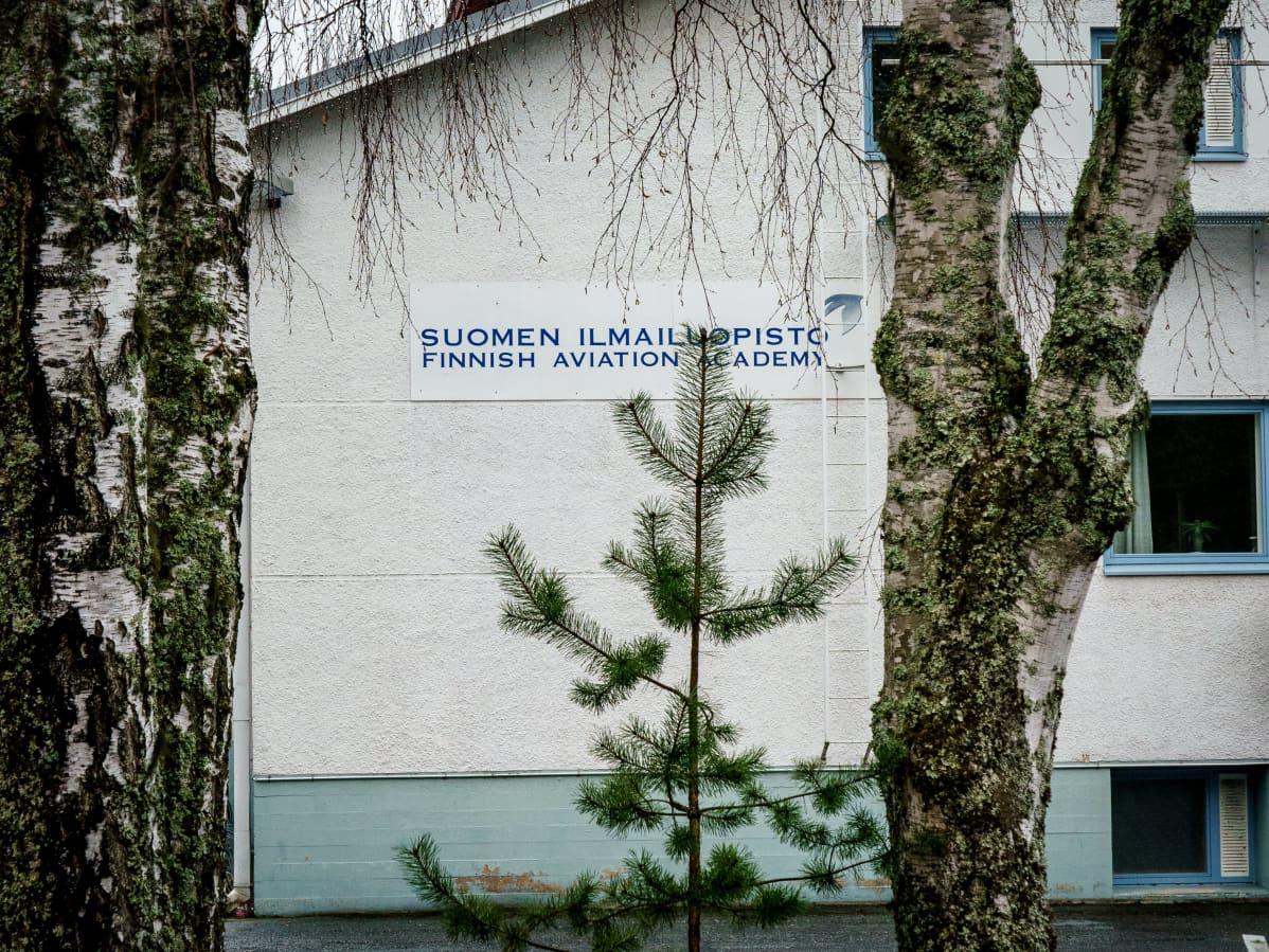 """Suomen Ilmailuopiston rakennuksen pääty, jossa teksti """"Suomen Ilmailuopisto""""."""