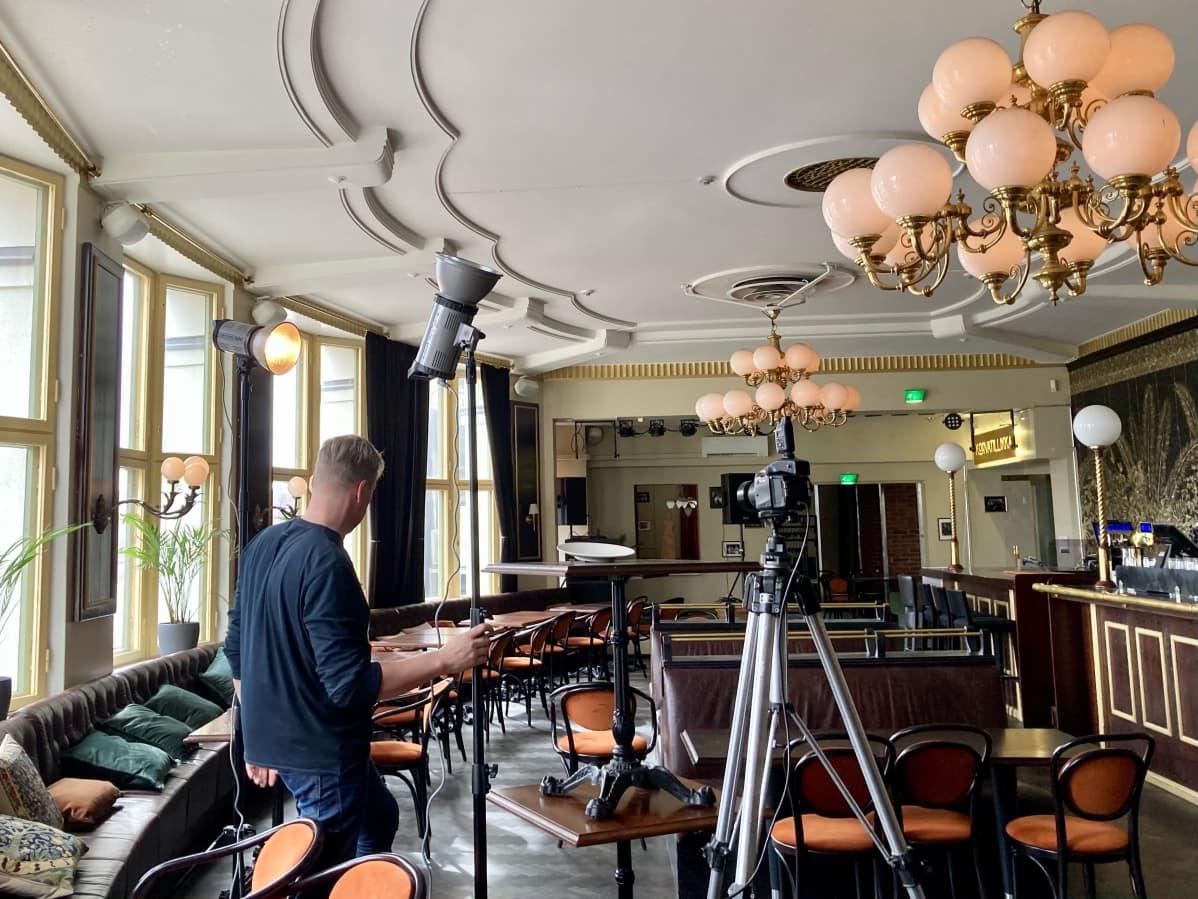 Valokuvaaja Harri Hinkka kasaa pöytiä päällekkäin ja asettelee valoja ravintola Tillikassa.
