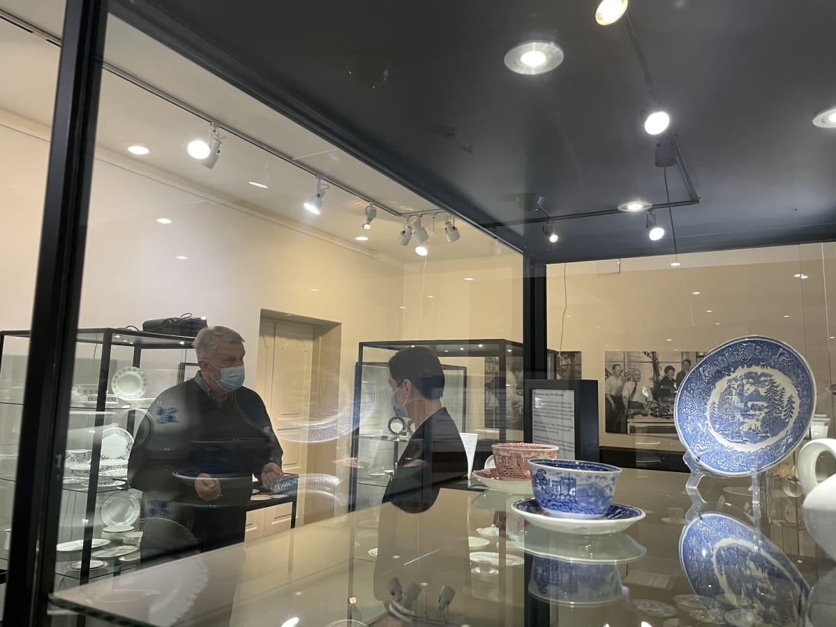 Pekka Annala ja Leni Koukkari puhuvat vitriinin takana, jossa on esillä vanhoja Arabian astioita.