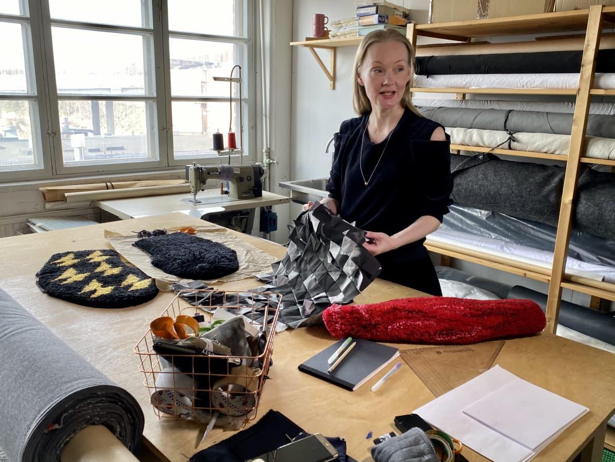 Irrotettavia hihoja erilaisista materiaaleista vaatesuunnittelija Marjut Uotilan työpöydällä.