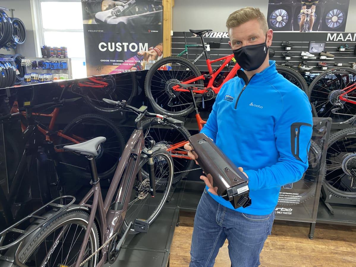 Lahden polkupyörähuollon myyjä Mikko Hirn esittelee sähköavusteisen pyörän akkua.
