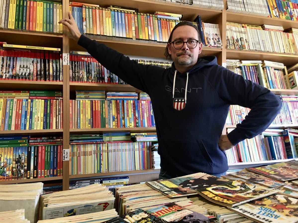 Harri Tastula sarjakuvahyllyjen edessä.