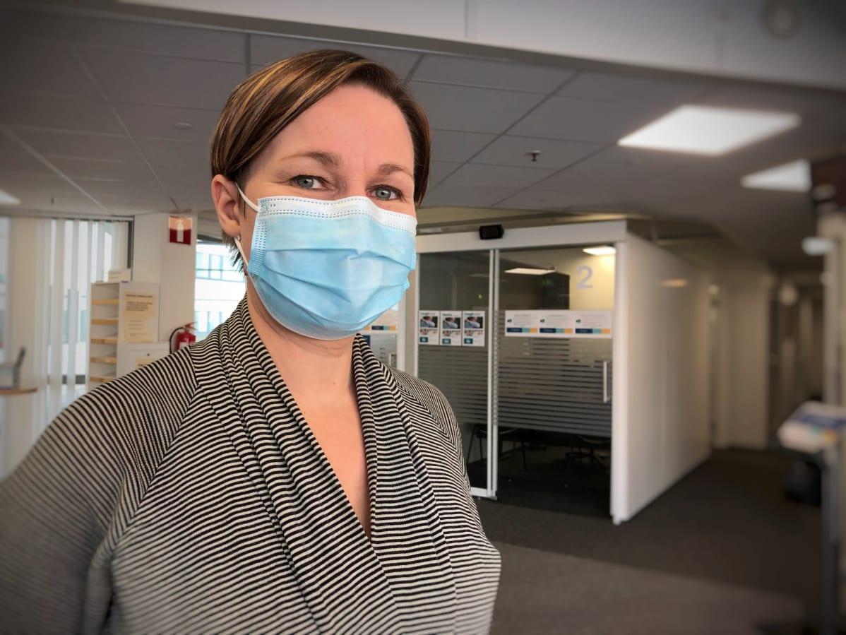 Nainen maski kasvoillaan seisoo tyhjässä odotushuoneessa. Taustalla palvelukoppeja.
