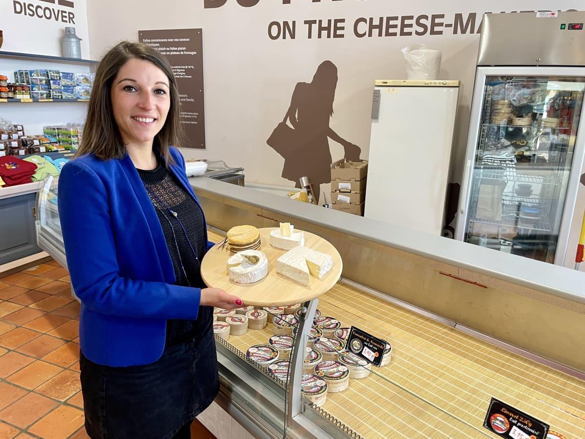 Nainen poseeraa juustotarjottimen vieressä