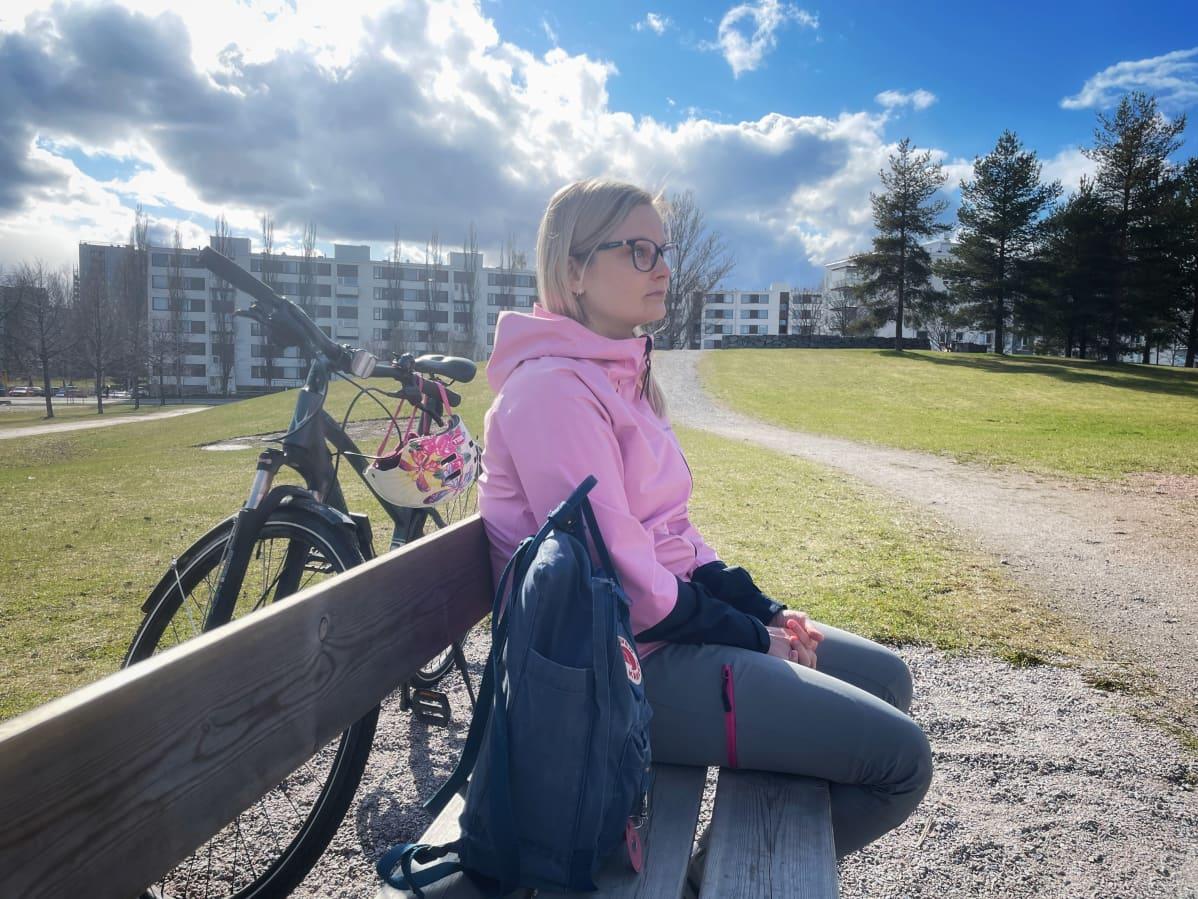 Mari Reunanen istuu puistonpenkillä, takanaan polkupyörä.