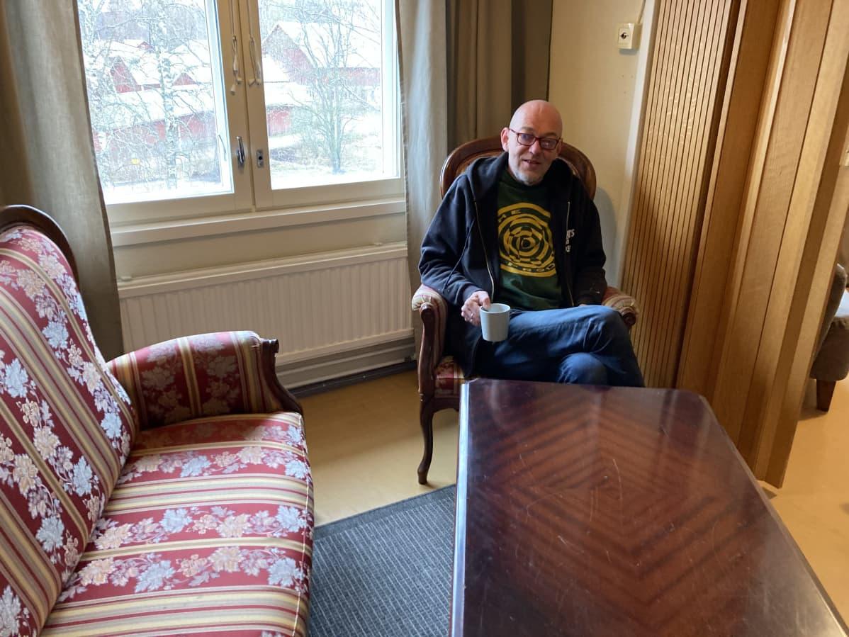 Kuva Pyhtään kulttuuritalon sisätiloista. Vesa Ristimäki istuu nuojatuolissa kahvikuppi kädessään.