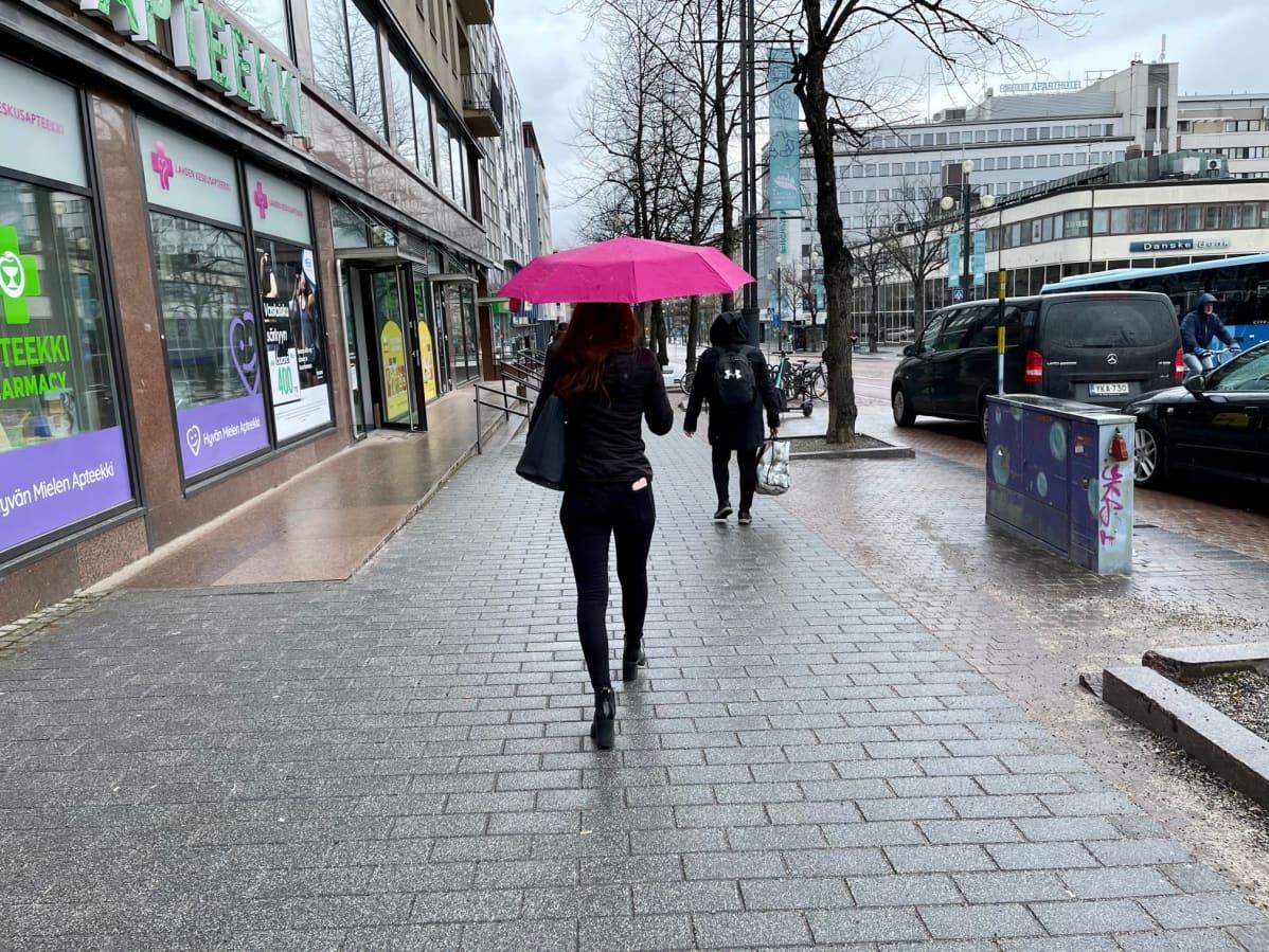 Nuori nainen pitää aniliininpunaista satenvarjoa ja kävelee kadulla poispäin kamerasta