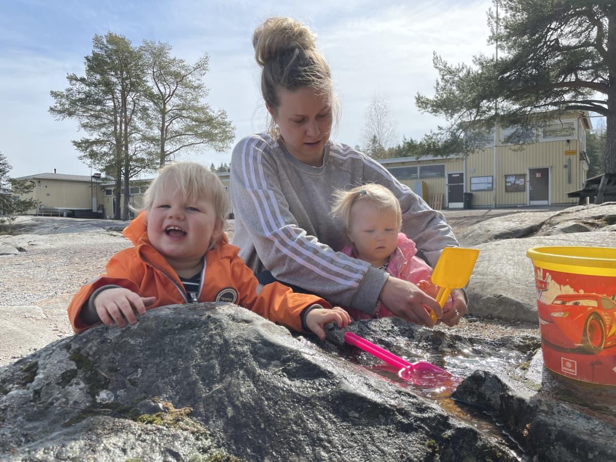 Annika Kuronen lastensa kanssa hiekkaleikeissä.