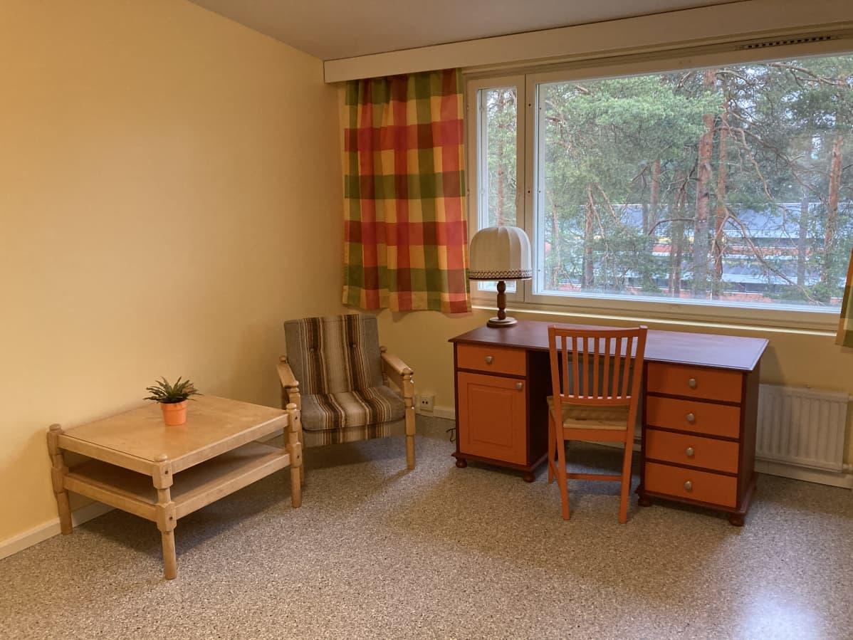 Ksaon hostellihuone. Pöytä, nojatuoli, työpöytä.