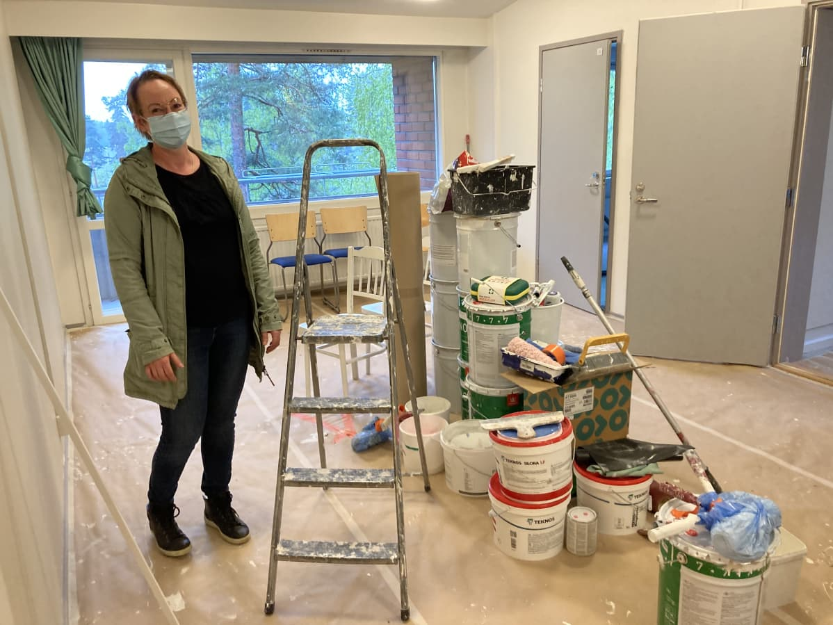 Ksaon Marika Hänninen seisoo remontoitavan huoneen keskellä. Lattialla kasa maalausvälineitä.
