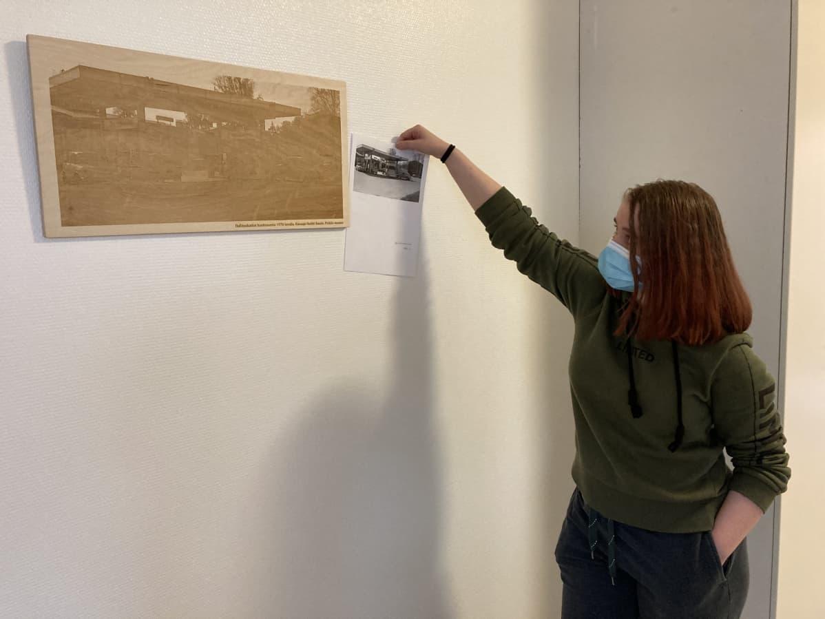 Tyttö esittelee puista taulua seinällä.