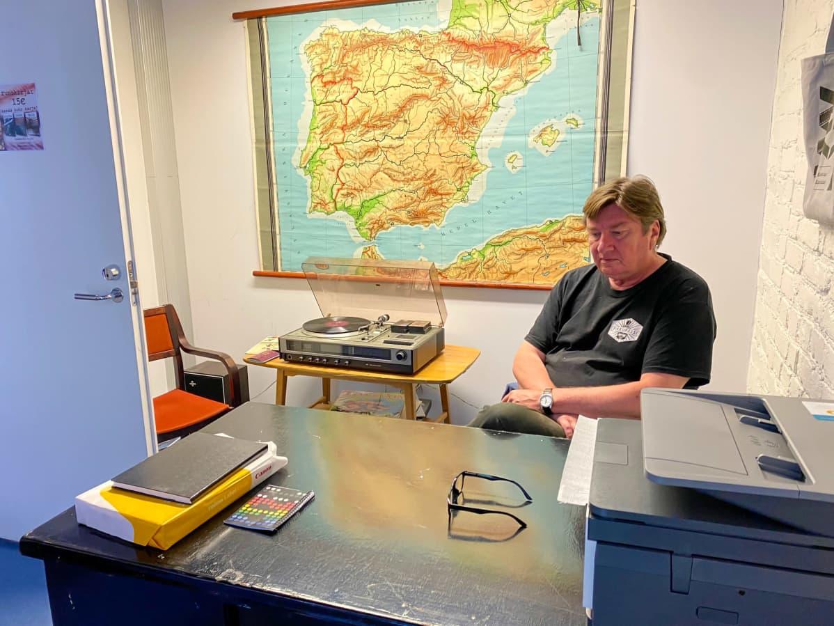 Aki Kaurismäki istuu toimistossa