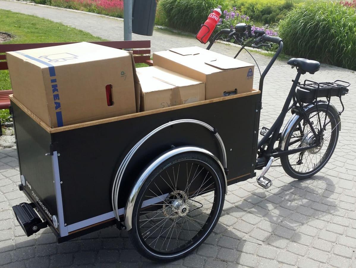 Polkupyörä, jonka kuljetuslaatikossa on pahvilaatikoita