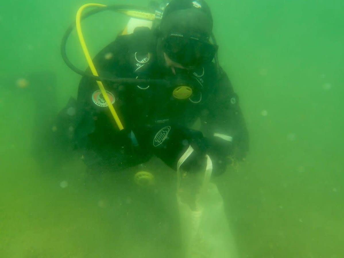 Sukeltaja kerää muovipussiin roskaa veden alla.