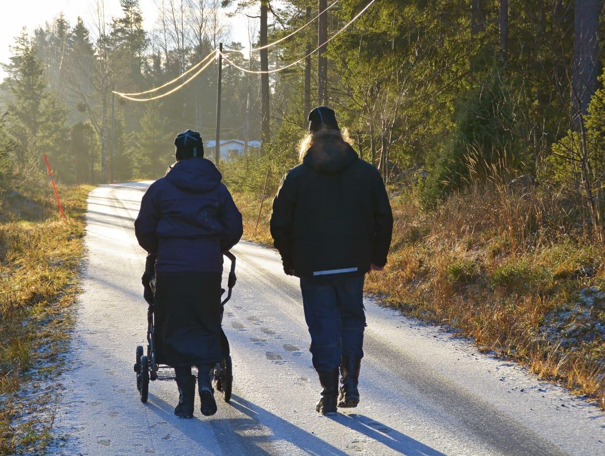 Kvinna och man promenerar med barnvagn på en frostig väg.