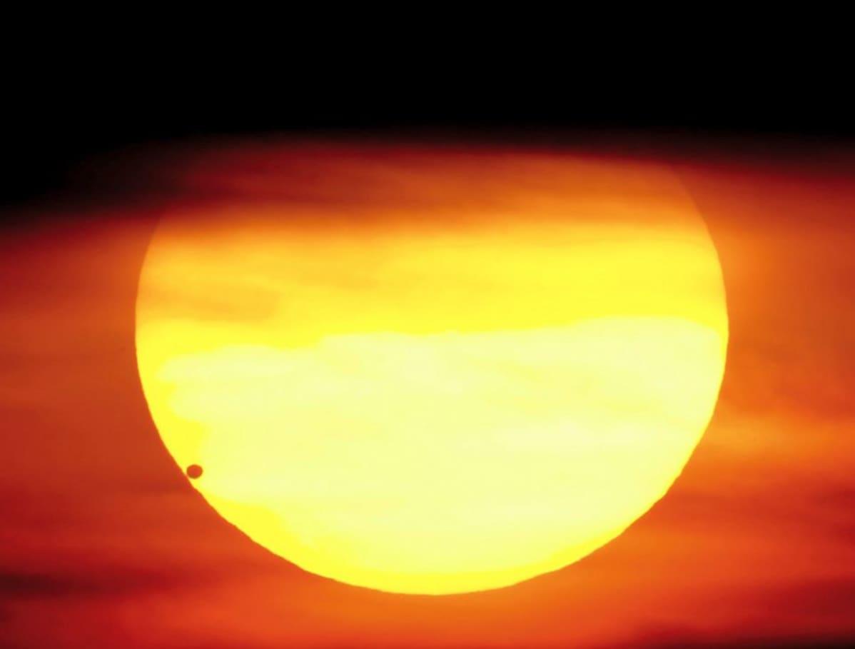 Venus tummana pallona auringon alareunassa.