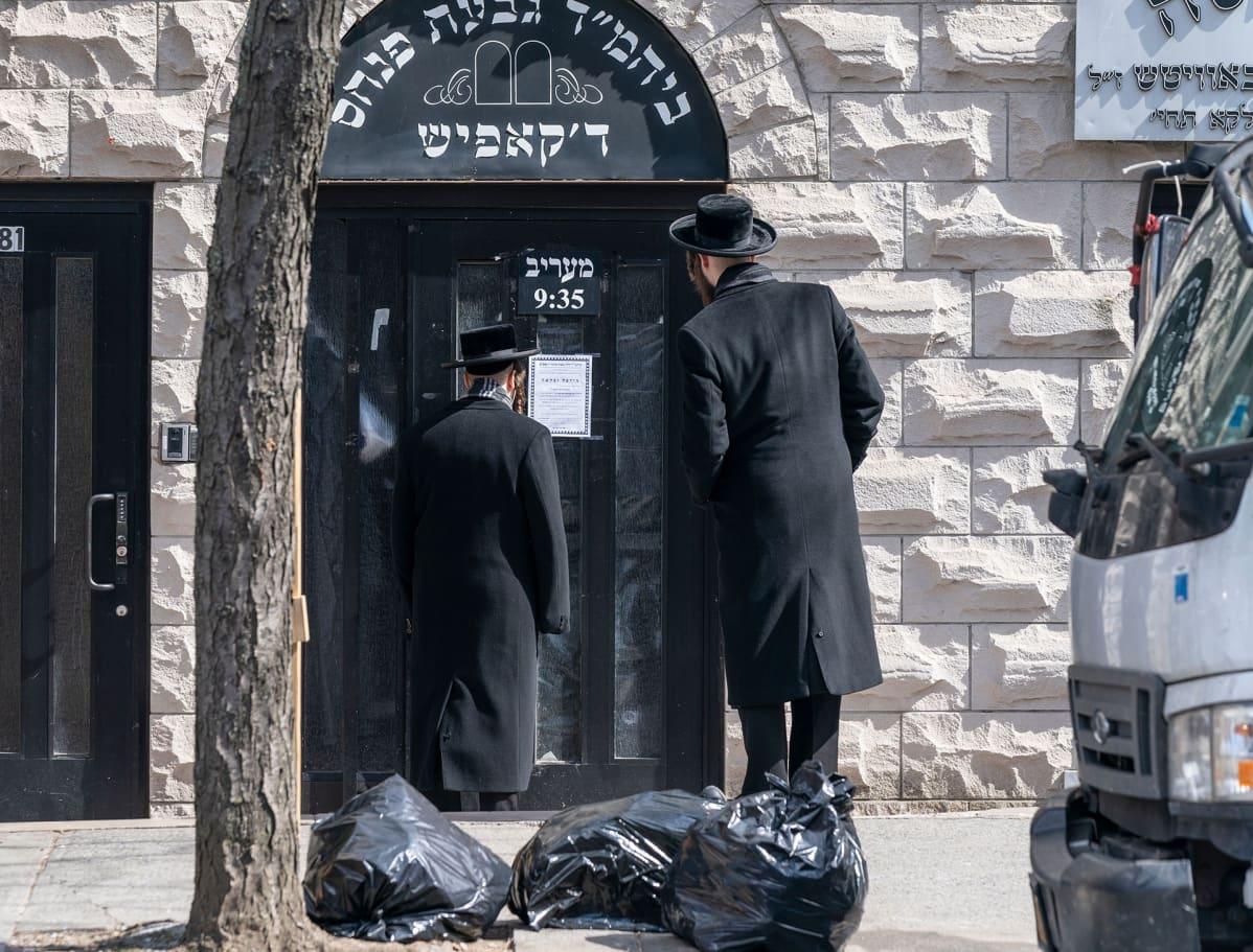 Hasidimiehet lukevat ilmoitusta koronavirksen sulkemasta synagogan ovesta.