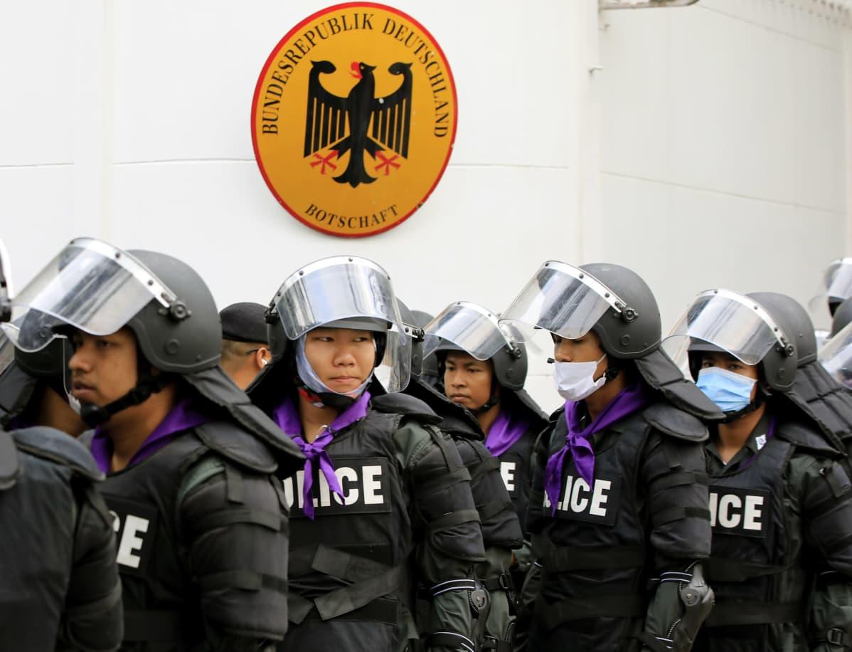 Kypäräpäiset poliisit Saksan suurlähetystön kyltin edessä.