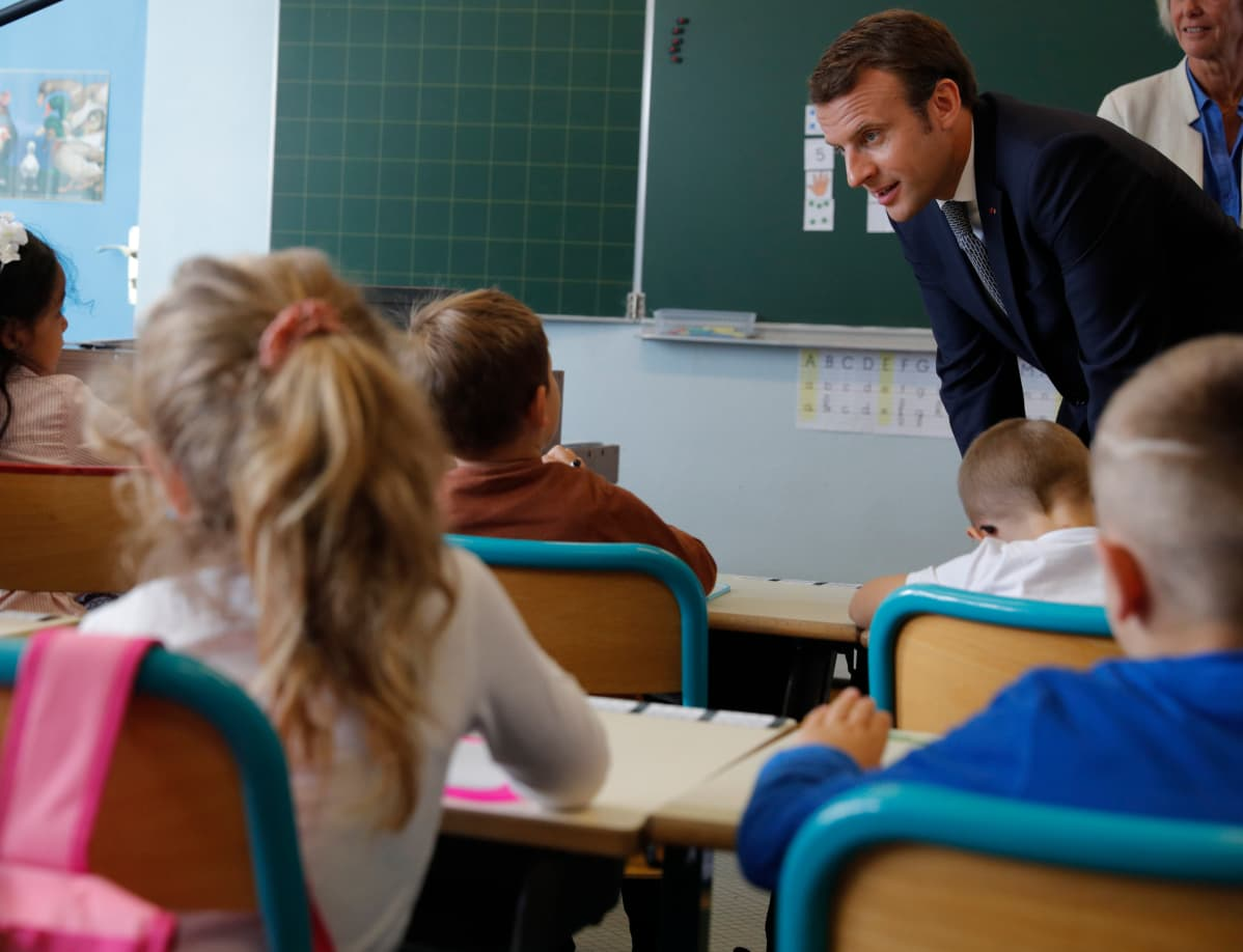 Presidentti Emmanuel Macron kumartuneena puhumaan pulpeteissa istuville pienille koululaisille.