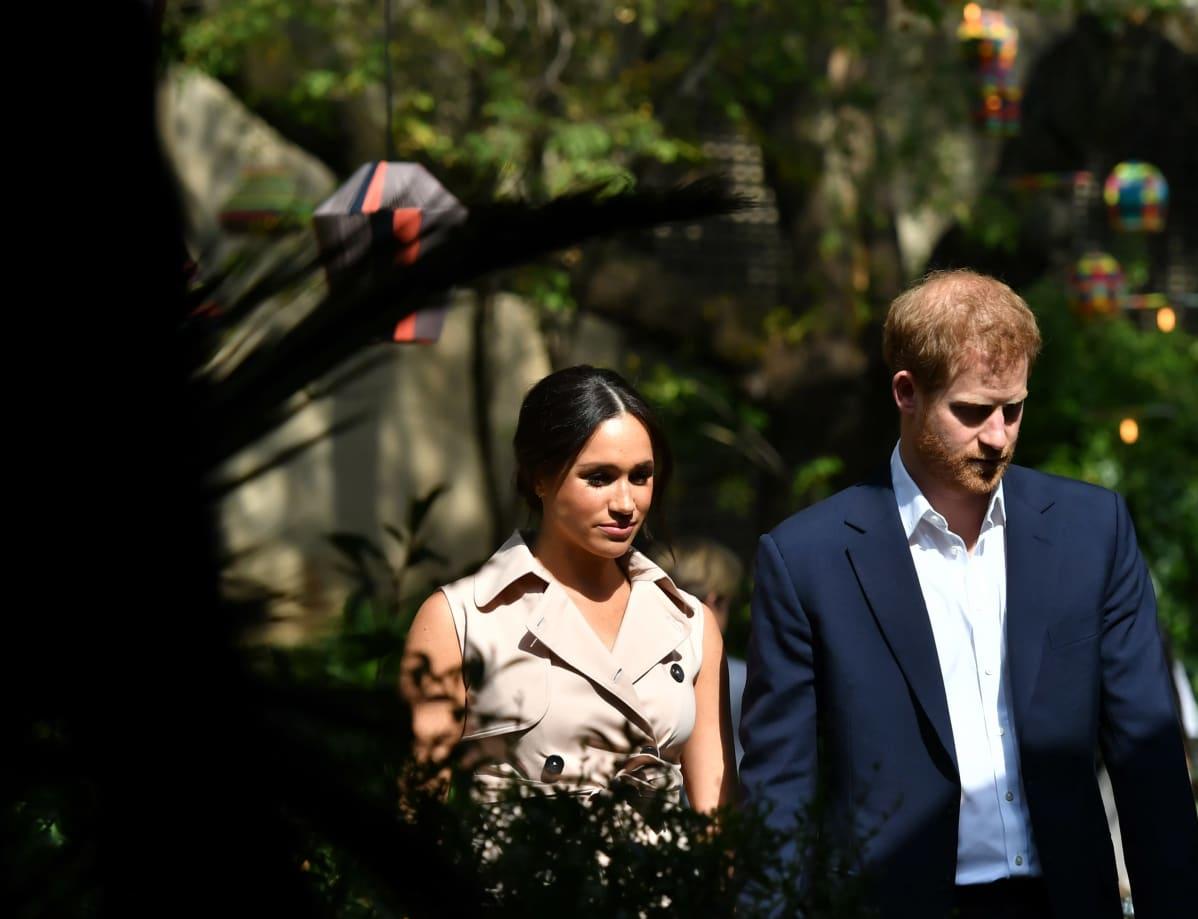 Herttuatar Meghan ja prinssi Harry kävelevät vierekkäin osin varjossa.