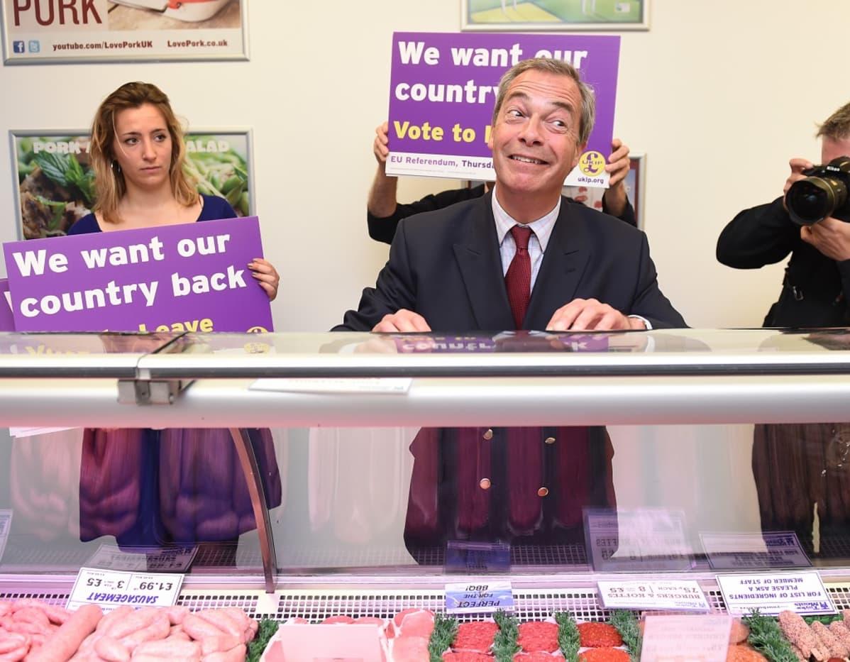 """Nigel Farage ilmeilee lihatiskin takana. Vieressä kannattajia, joiden kylteissä lukee englanniksi: """"Haluamme maamme takaisin""""."""