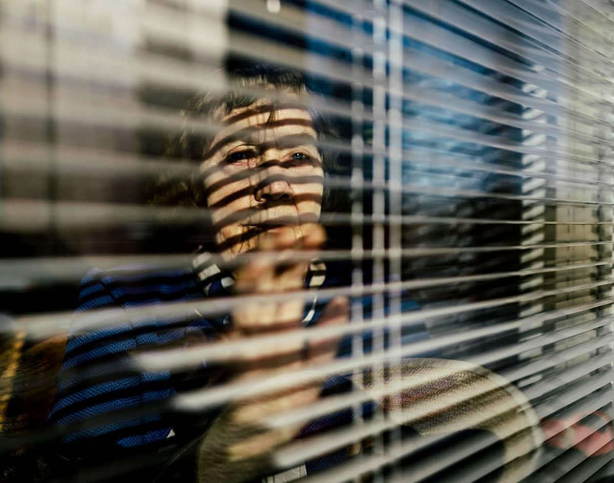 Paula Ollila katsoo ikkunan läpi