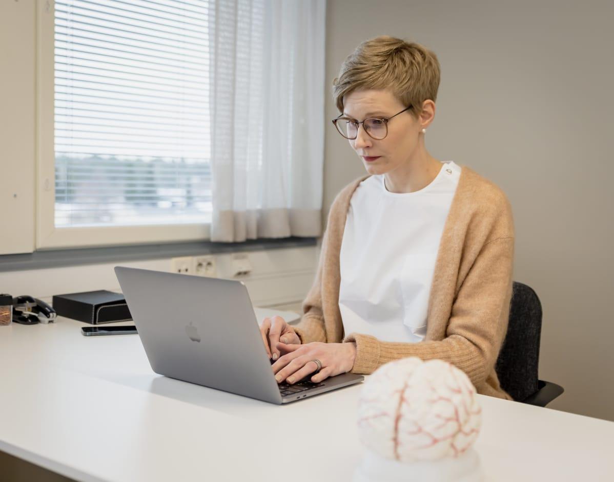 Hanna Kortteinen istuu tietokoneen ääressä. Pöydällä on muovinen malli aivoista.