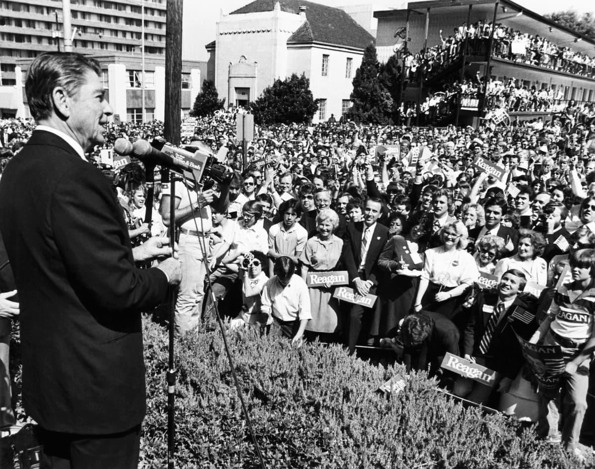 Mustavalkokuvassa Ronald Reagan puhuu yleisölle.