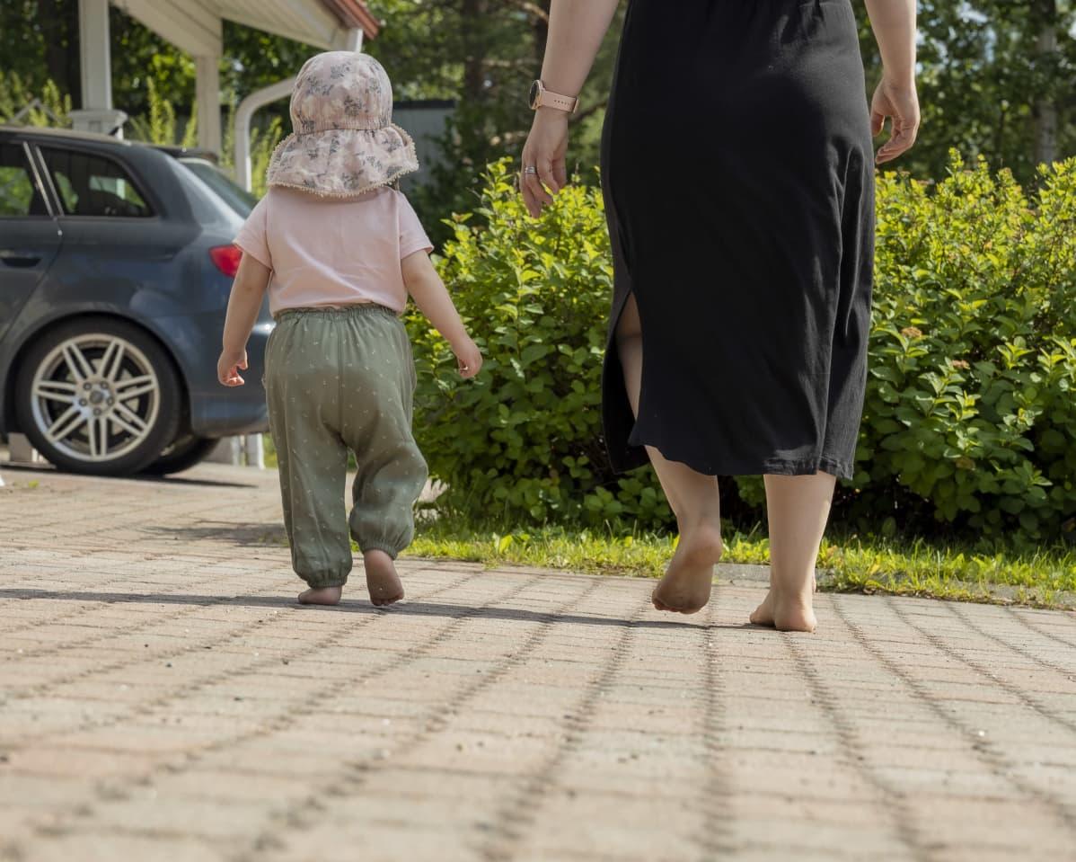 Äiti ja lapsi kävelevät paljain jaloin pihamaalla