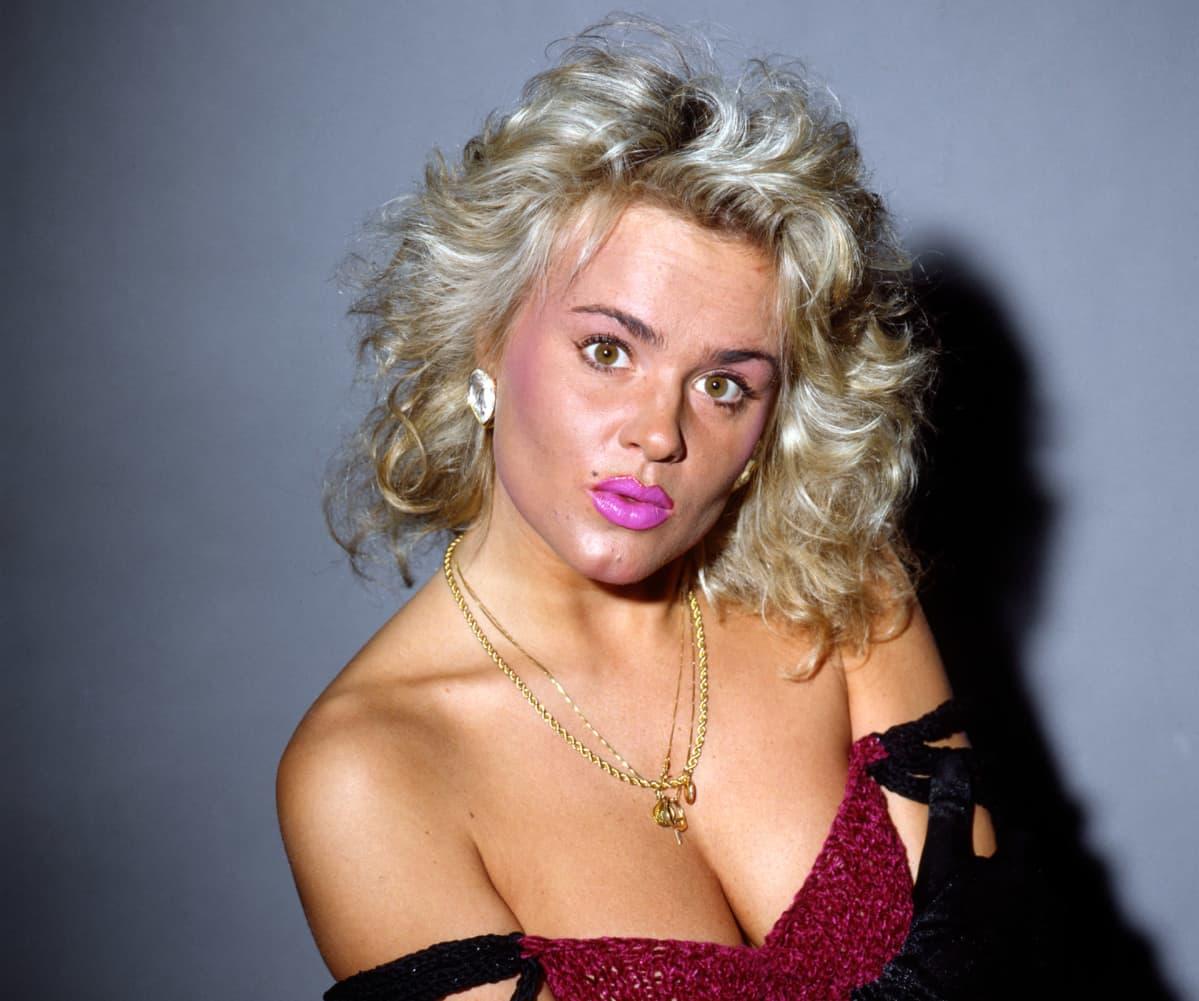 Kikka valkoista seinää vasten olkaimettomassa mekossa. Paljon meikkiä. Kuva vuodelta 1990.