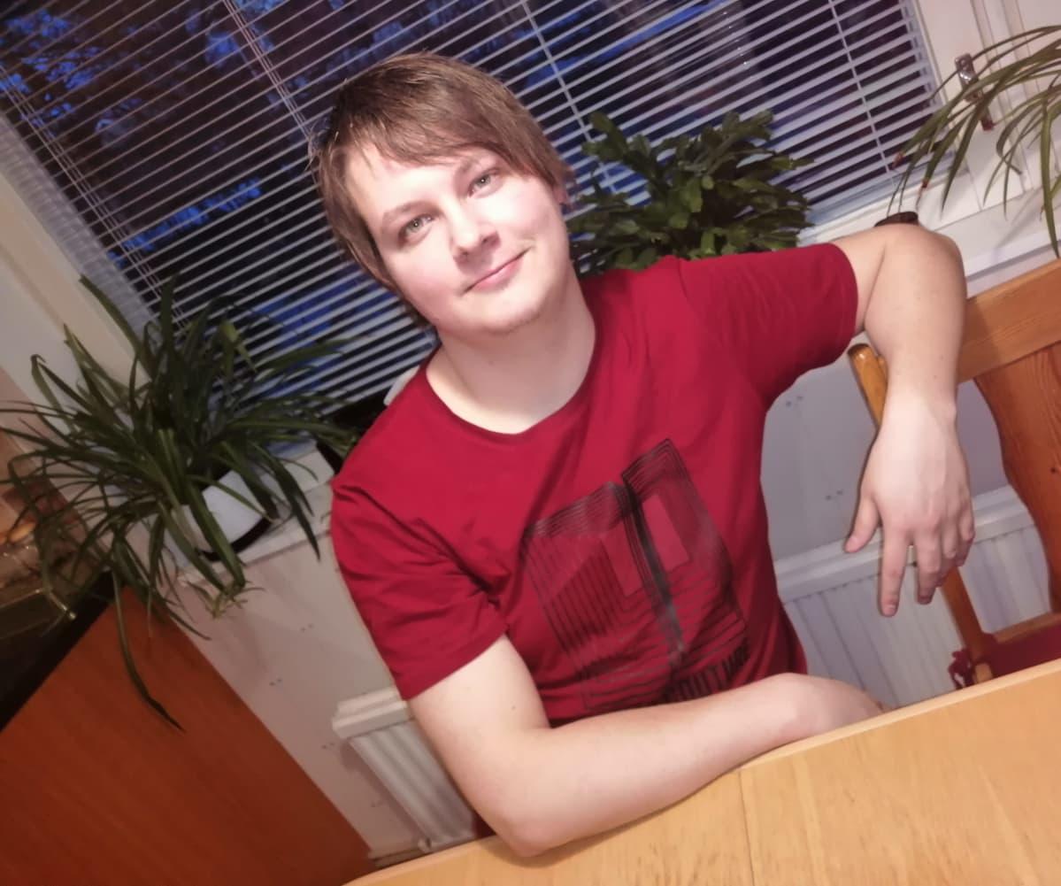 Tamperelainen Arttu Helenius istuu pöydän äärellä.
