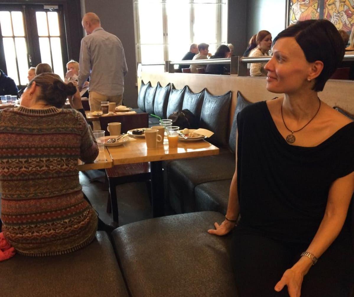 Naine istuu kahvilassa penkillä, taustalla ihmisiä.