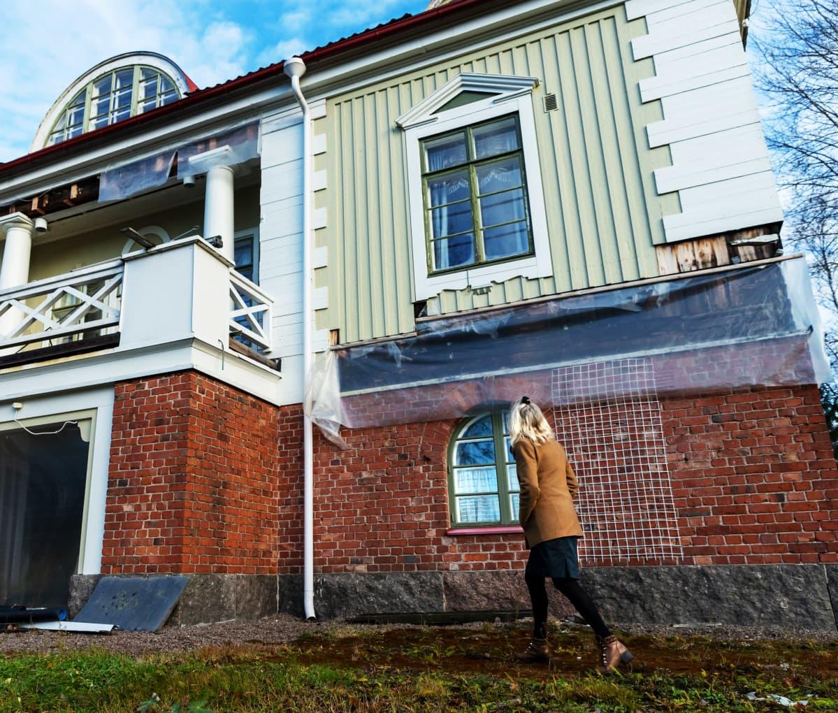 Terttu Aalto kävelee Villa Idan pihalla, katsoo huvilaa kohti.