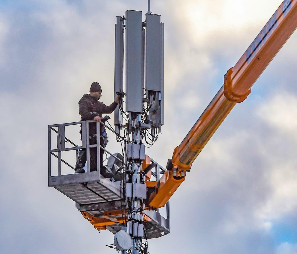 Teknikko asentaa puhelinverkon antennia talon katolle Freiburgissa.
