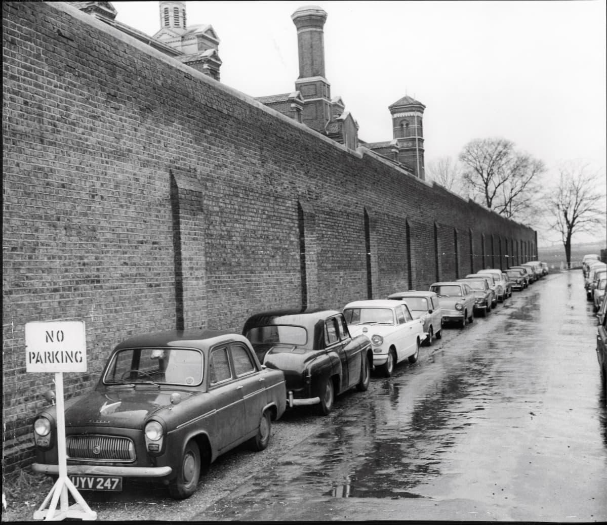 Mustavalkoisessa kuvassa näkyy vankilan  tiilimuuria. Sen eteen kadulle on parkkeerattu autoja.