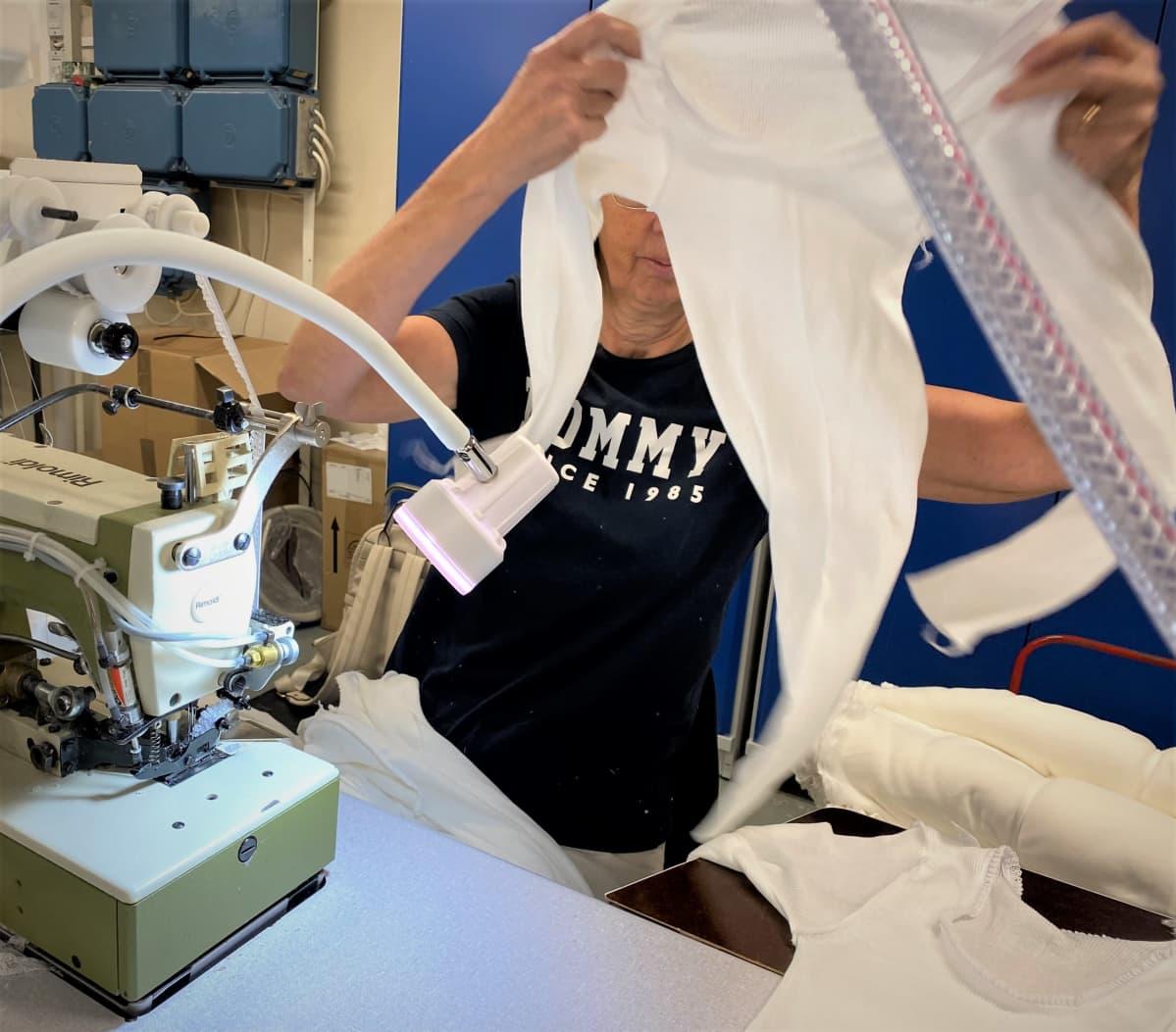 Nainen pitelee ompelemaansa laamapaitaa