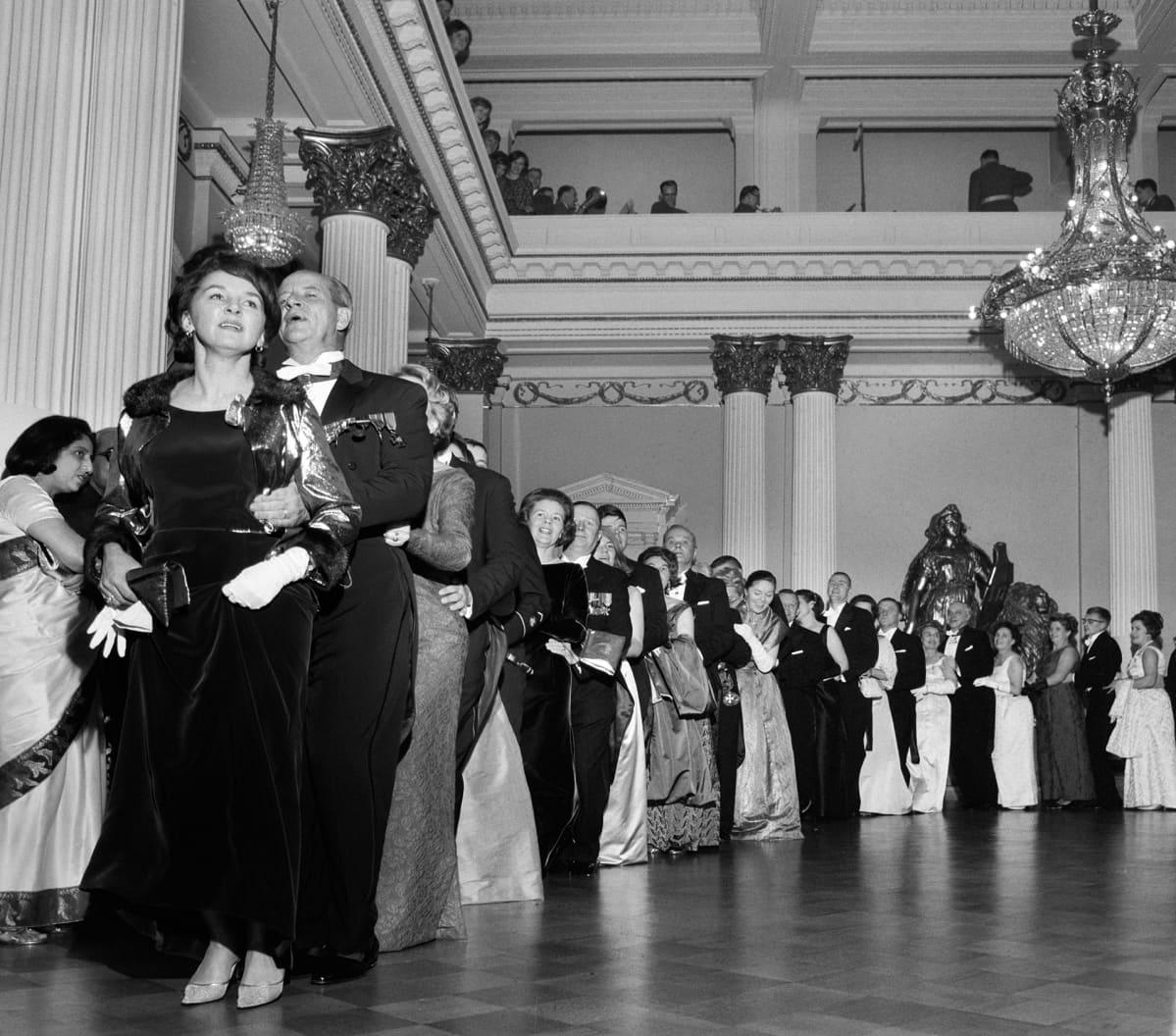 Juhlavieraita tanssimassa muotitanssi letkajenkkaa Linnan juhlissa 6. joulukuuta 1964.