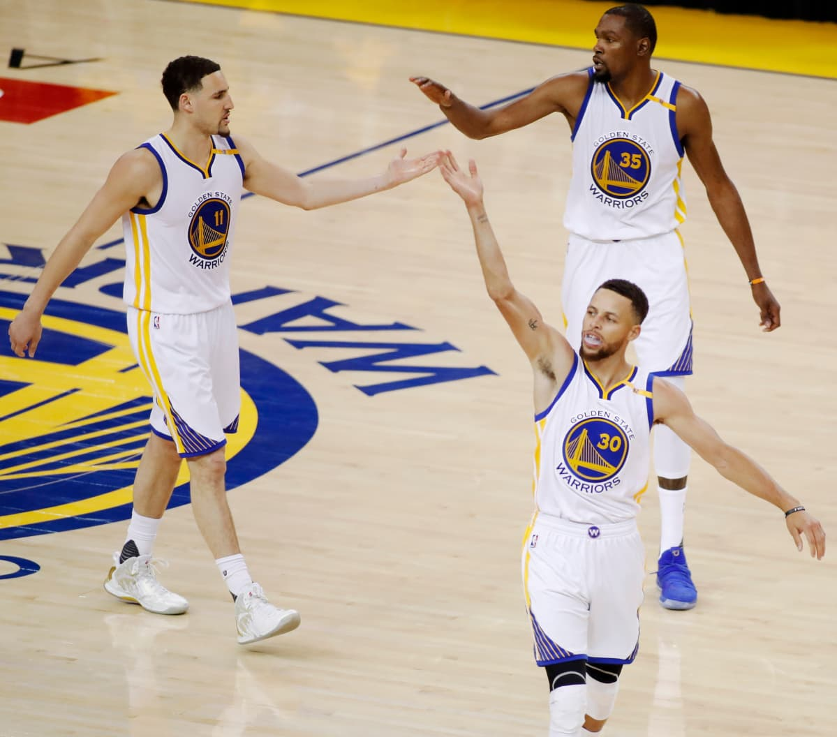 Golden State Warriorsin Stephen Curry, Klay Thompson ja Kevin Durant juhlivat voittoa.
