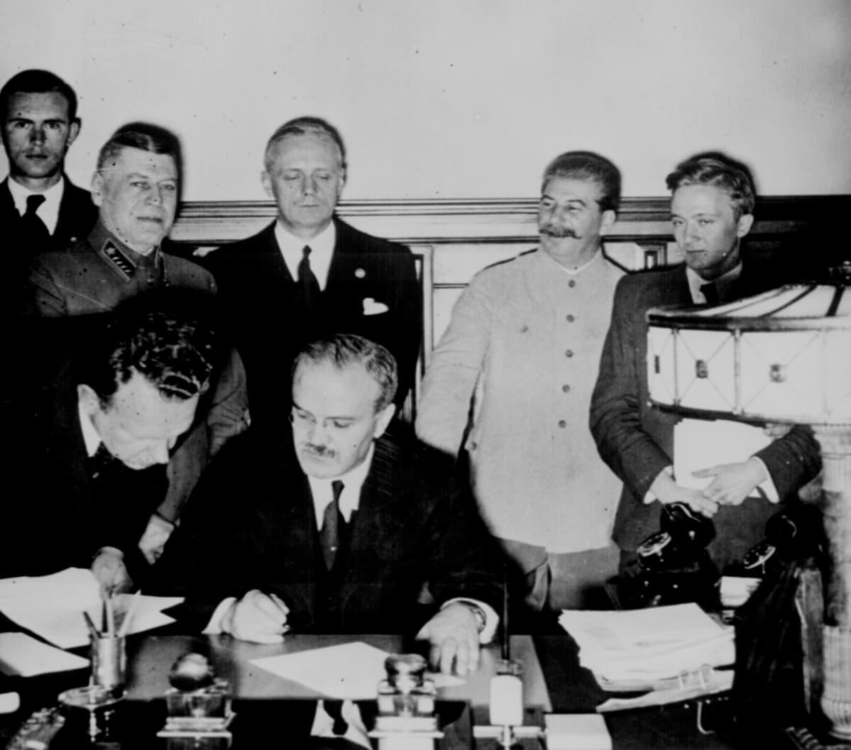 Molotov istuu pöydän ääressä allekirjoittamassa. Hänen takanaan seisoo Ribbentrop, vakavana. Stalin hymyilee vieressä univormussaan.